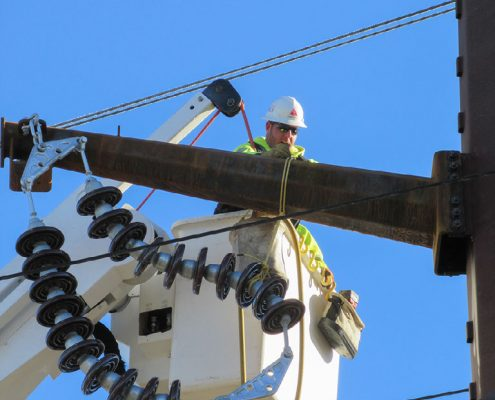 Outside lineman in bucket working on high-voltage transmission pole